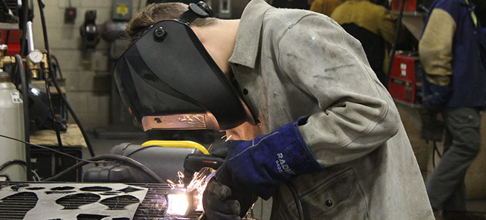 One student welder working with a torch and metal object.