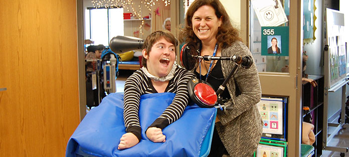 Smiling student with Physical Therapist with an assistive technology device for speaking