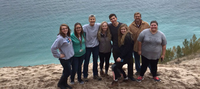 NTHS Student Officers and adult advisors standing on the sandy bluff at Pyramid Point overlooking Lake Michigan in Empire, Michigan.