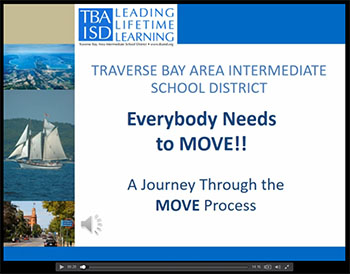 TBAISD logo with photos of a tall ship with sails  and downtown Traverse City Michigan.
