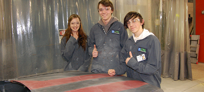 Two boys and a girl standing in automotive lab showing the hood of a car that is being repaired and painted.