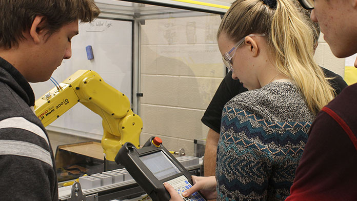 male and female students working on a robotic control arm.