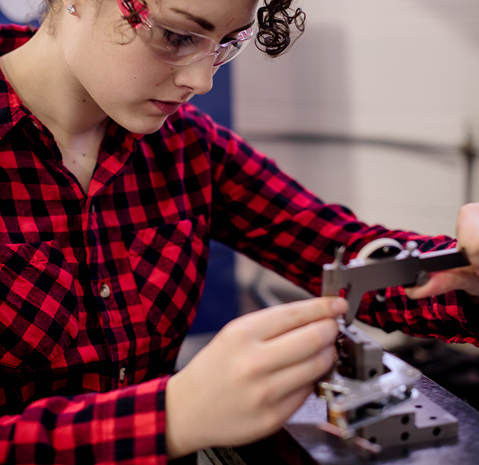 female student making a precise measurement on tool bench