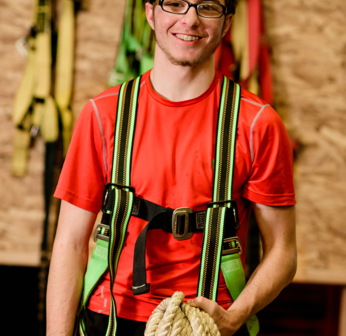 Male student holding rope and wearing rooftop harness system