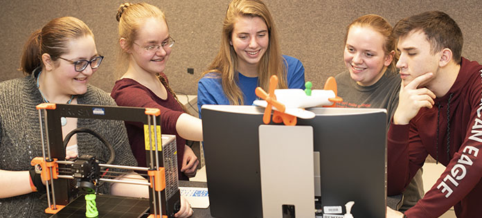 Five students working as a team in front of a 3D printer and a computer monitor.