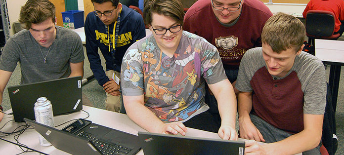 Team of five students working on internet security challenge project.