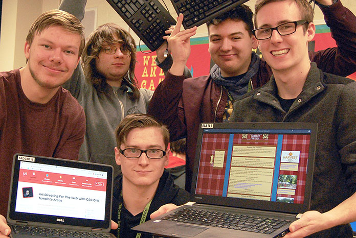 five smiling students, two laptops showing websites that have been designed by students.